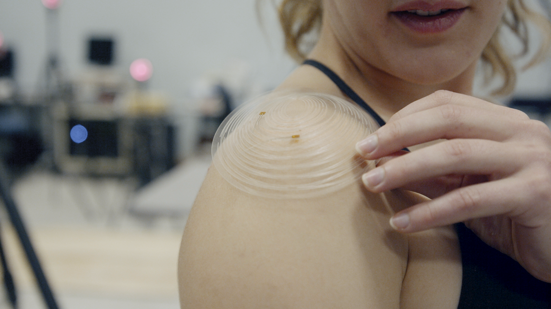 Erin Evke demonstrates how the cut patterns in the kirigami sensor open so that it follows the curve of her shoulder. This enables the sensor to be manufactured flat, which is crucial to making the device affordable. Credit: Levi Hutmacher, Michigan Engineering