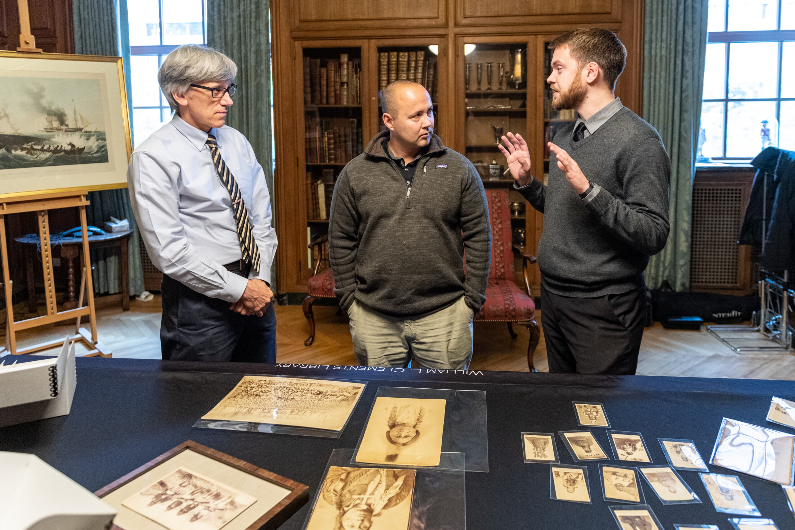 Left to right: Clayton Lewis, Eric Hemenway, and Jakob Dopp look at images from the Richard Pohrt Jr. Collection of Native American Photography at the William L. Clements Library. Image credit: Scott Soderberg, Michigan Photography