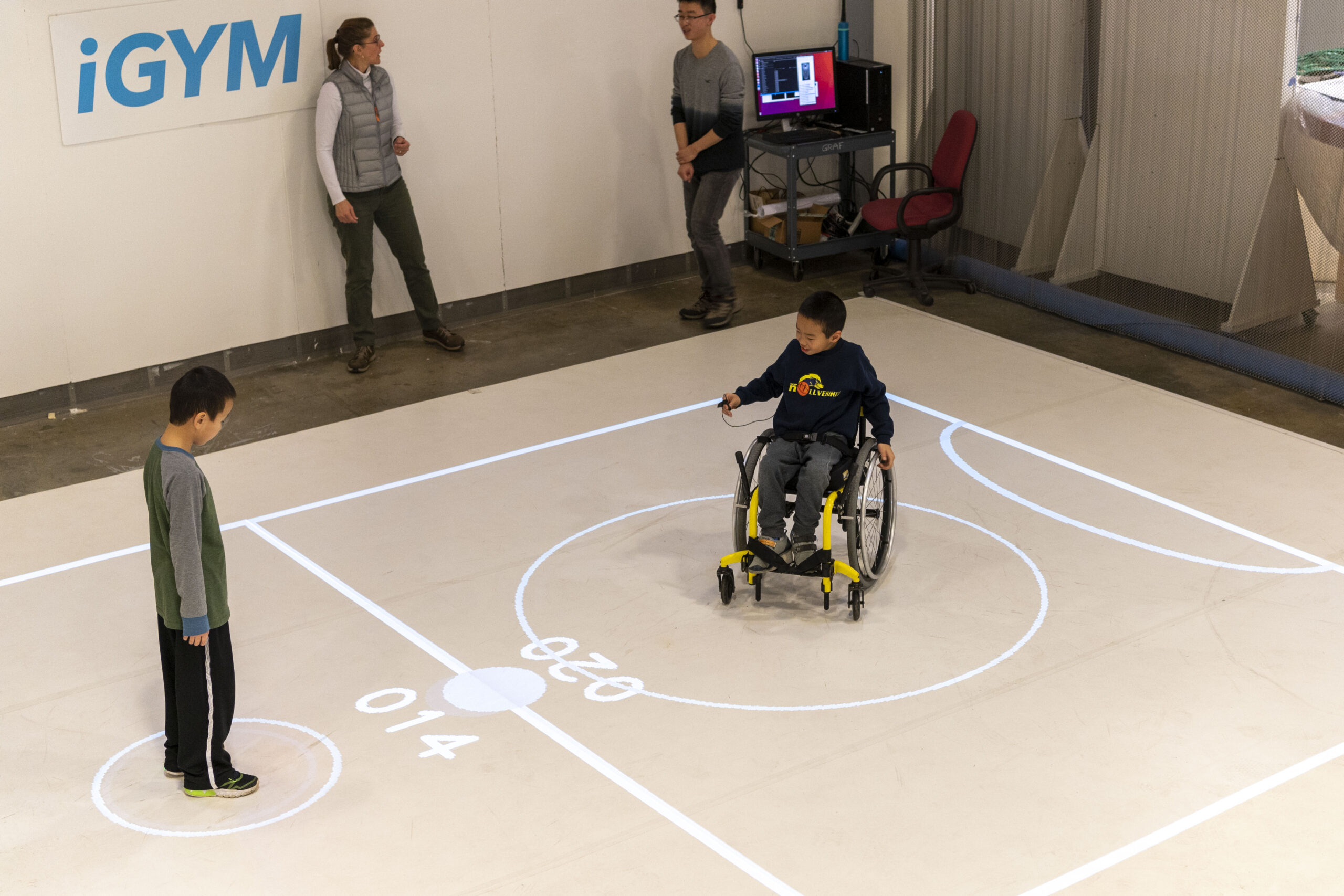 "Darren Kreps (left) and his brother Bryan Kreps participate in a ""play test"" of iGym, an augmented reality system created by a multidisciplinary team at the University of Michigan that promotes inclusive play and exercise. Image credit: Roger Hart/Michigan Photography."