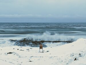 Waves break against the shore in the wintertime Arctic, leading to sea spray aerosols. Image credit: Kerri Pratt