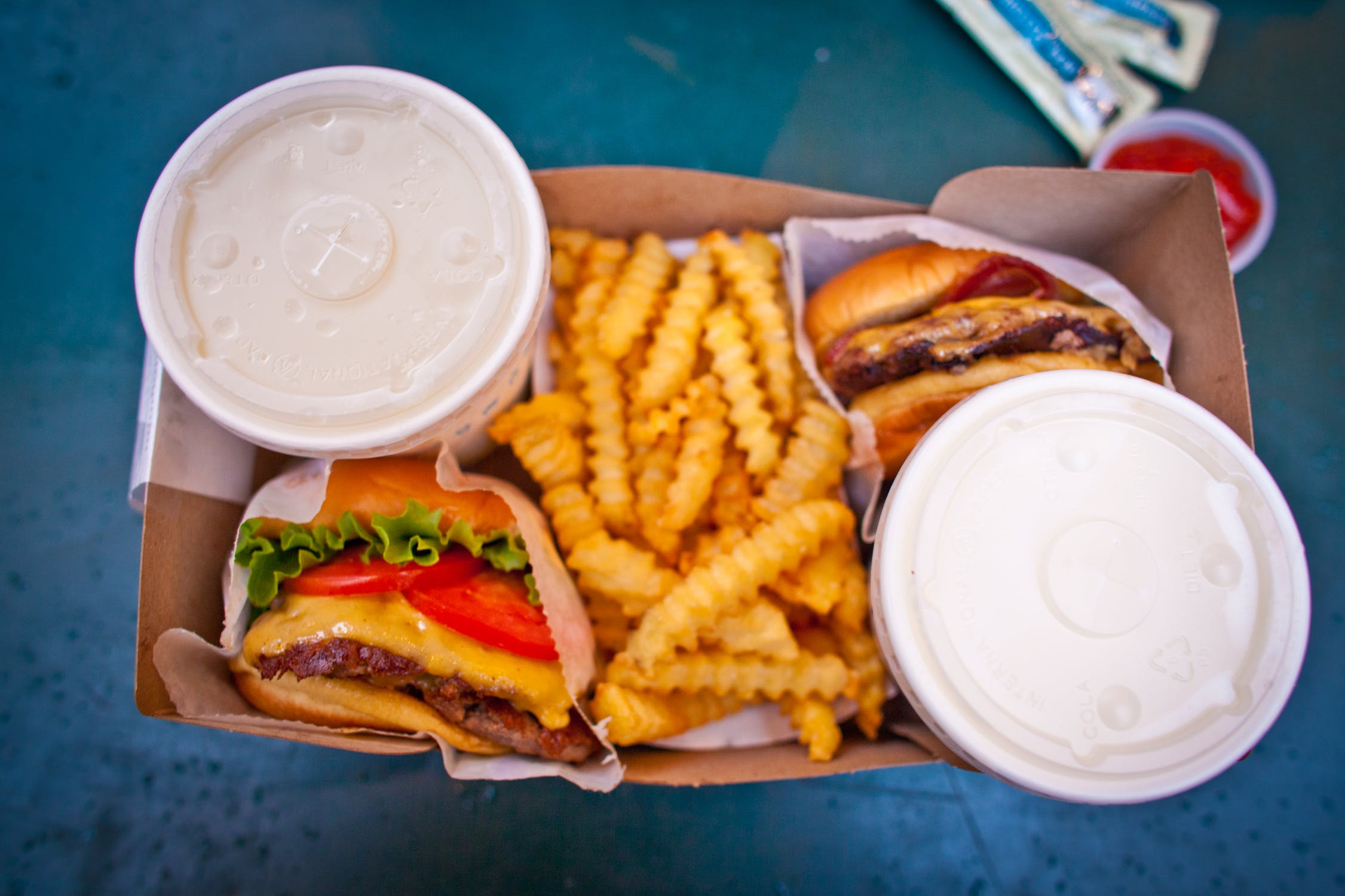 A box with burgers, fries and soda.