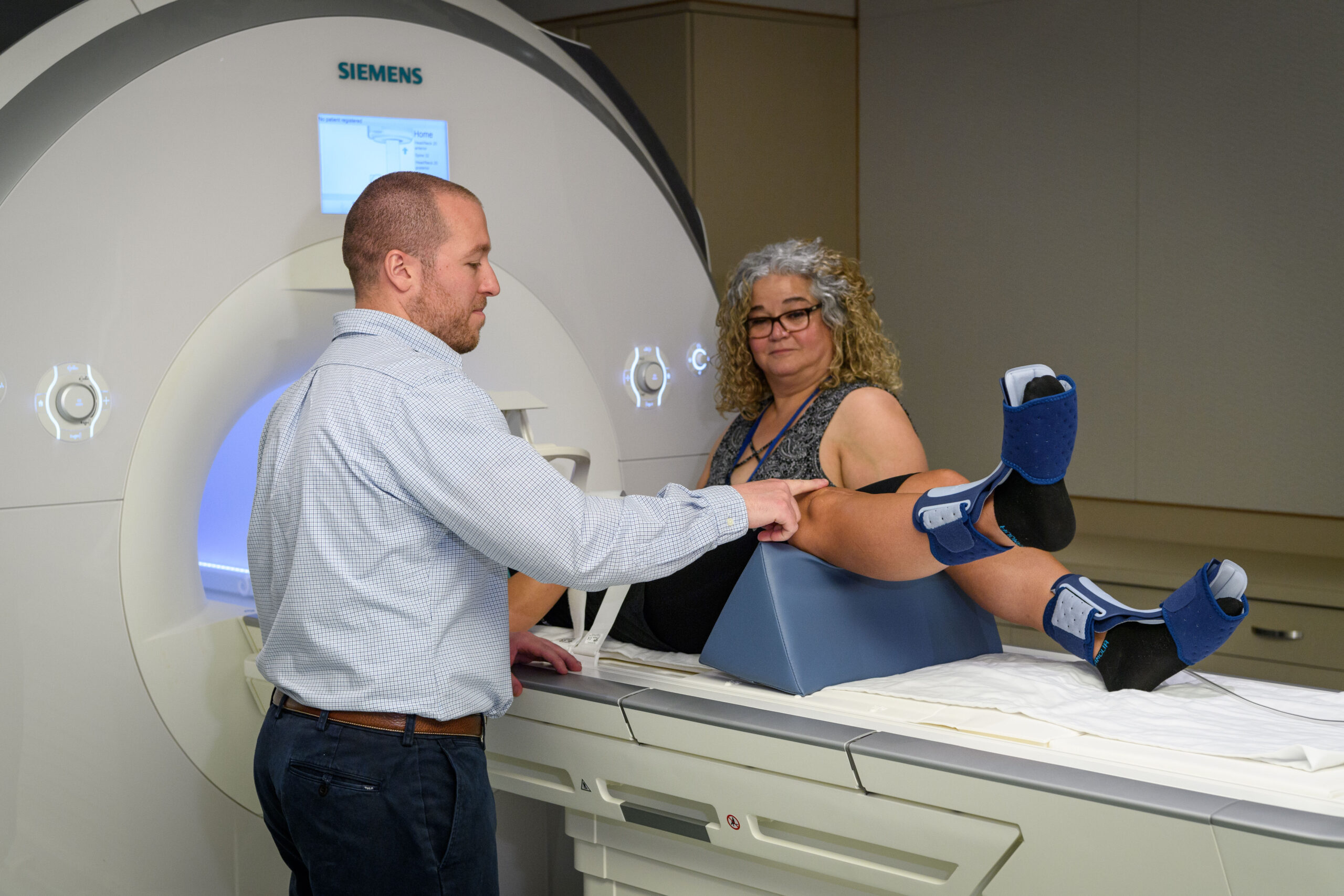 Lepley points to the knee of the patient laying on the MRI examination table, while Medeiros looks on from the other side of the table , while