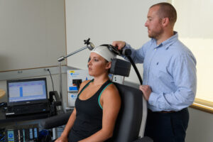 Adam Lepley, assistant professor of kinesiology, prepares a model subject for transcranial magnetic stimulation at the Phillips Communication Sciences Building, University of Connecticut, on July 17, 2017. Image credit: Peter Morenus