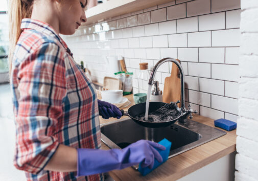 Young woman doing dishes. Image credit: iStock