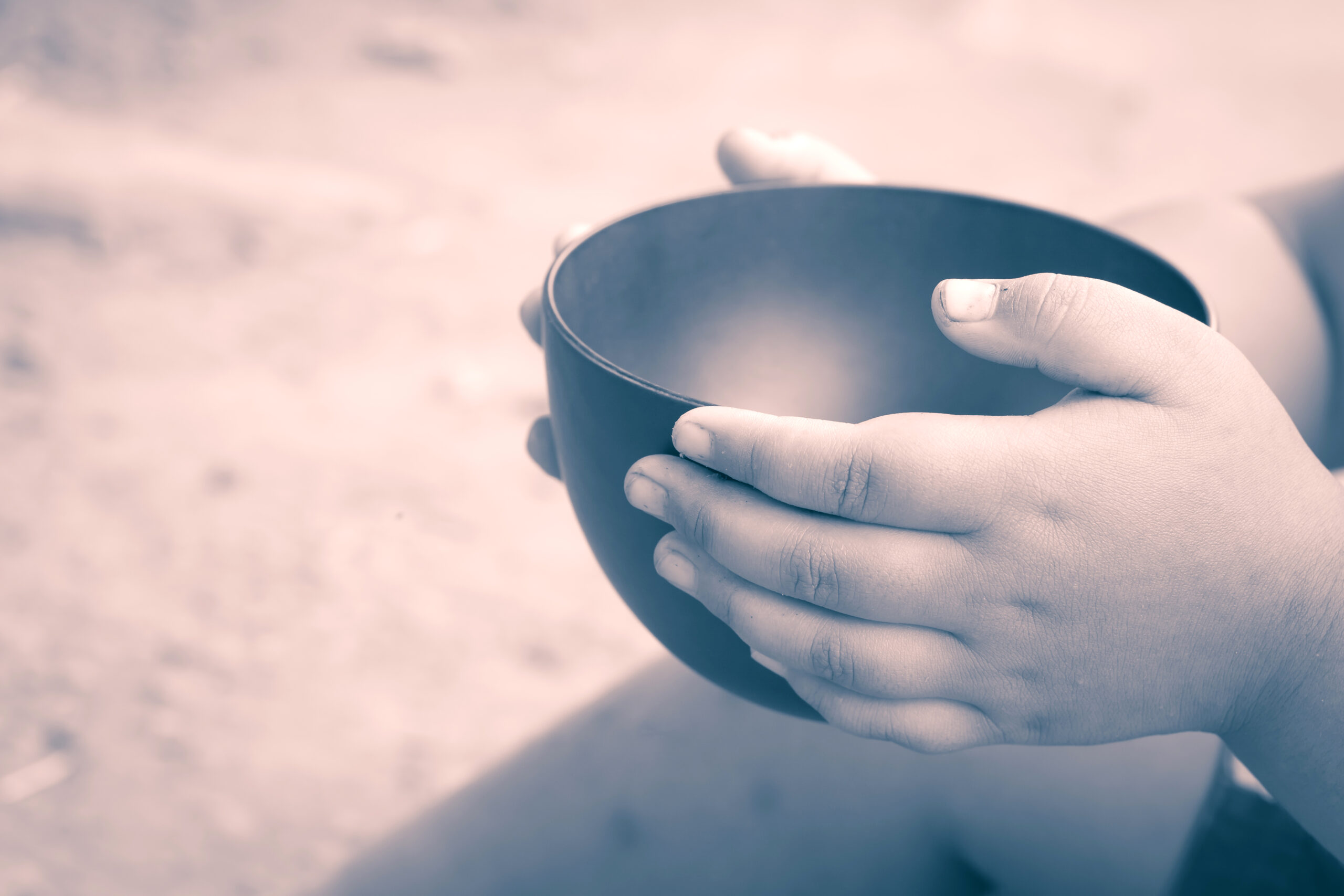 Image of a child holding an empty bowl.