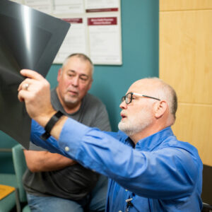 Howard Winchel (left) and Dr. Philip Baty discuss Winchel's X-ray. Image credit: Eric Bronson, Michigan Photography