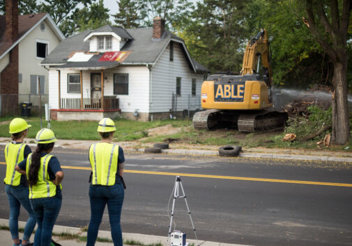 Workers look on as a home is demolished.