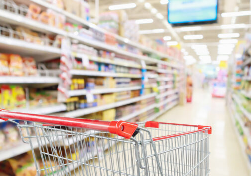 Empty shopping cart in a grocery store aisle. Image credit: iStock