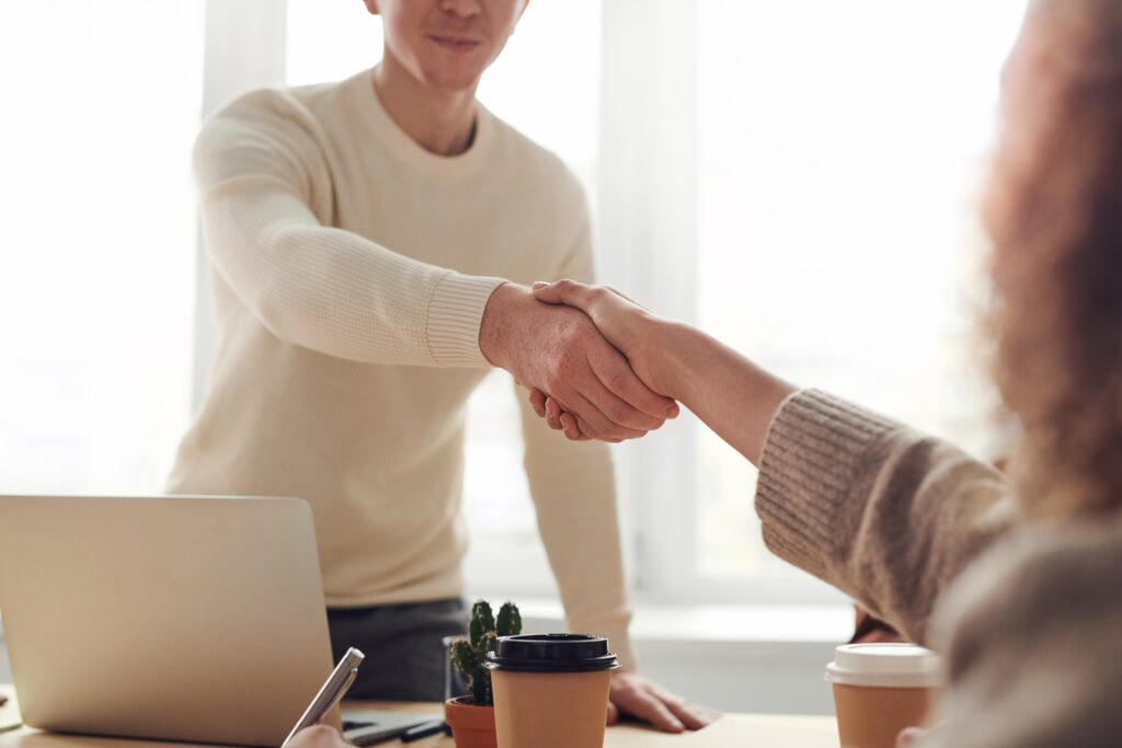 A man and woman shake hands over a desk. Image credit: Pexels.com user, fauxels