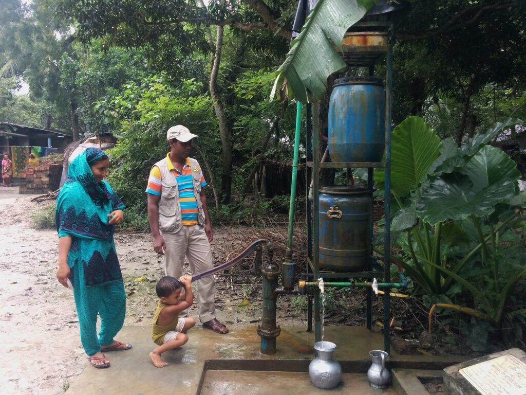Family collecting water from a smaller community safe drinking water device. Image credit: R. Reddy