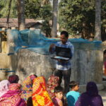 The team shares water quality results and information with community members e water from an arsenic-removing filter in Goga union. Image credit: R. Reddy