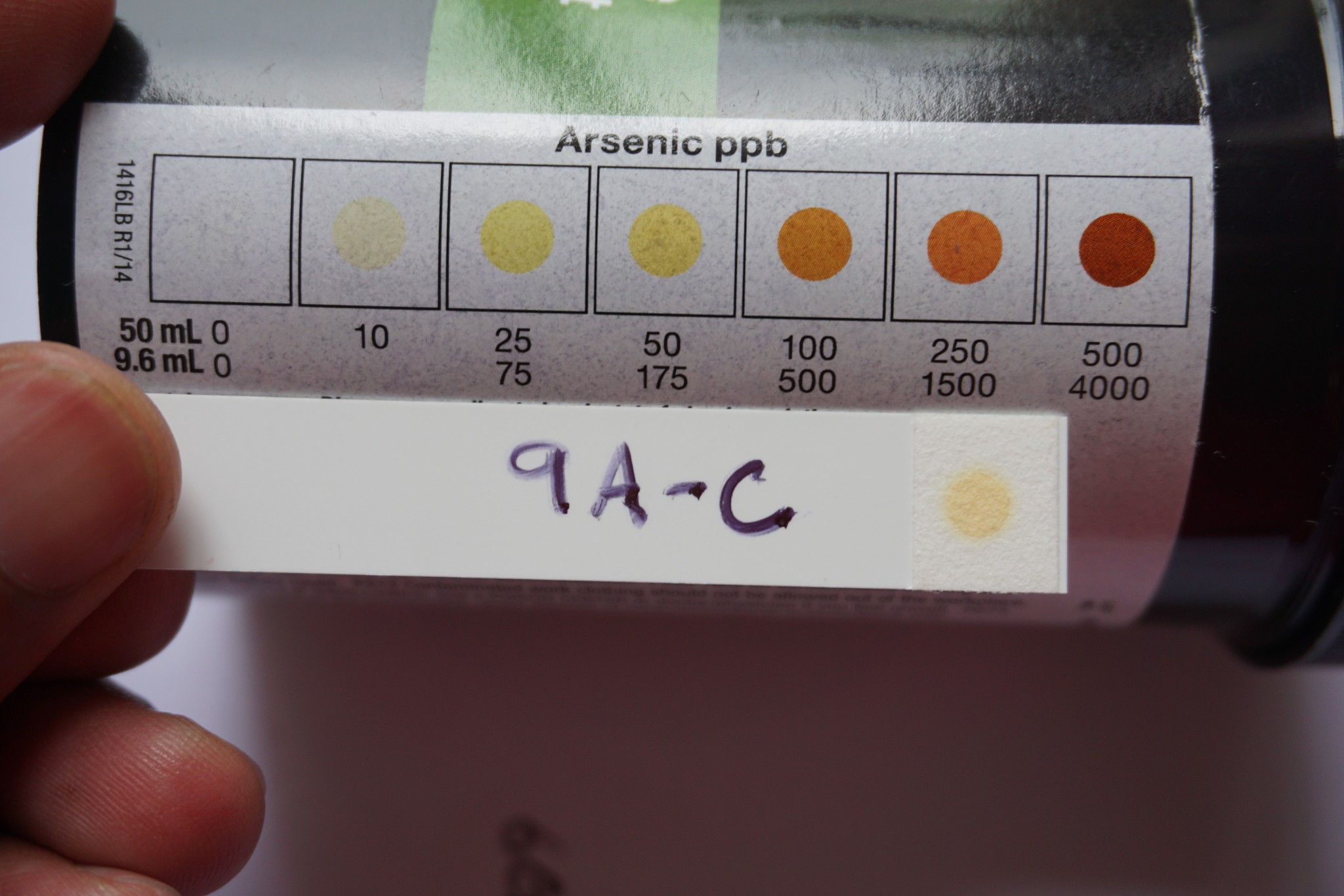 """A person holds a test strip labled """"9A-C"""" with a yellow dot at the end up to a chart showing light to dark colored dots indicating different levels of arsenic in water"""