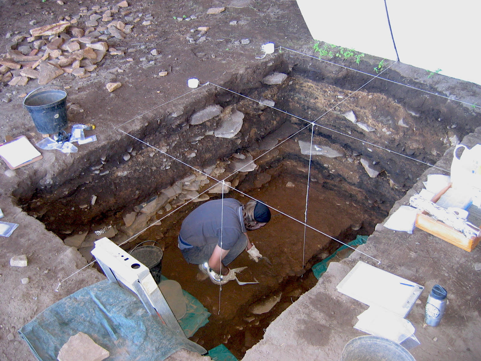 An archeologist crouches in a rectangular pit digging in the dirt