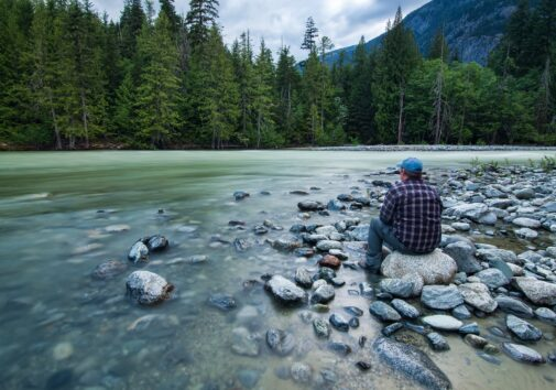 A man sits on a river bank. Image credit: jameswheeler via Pixabay