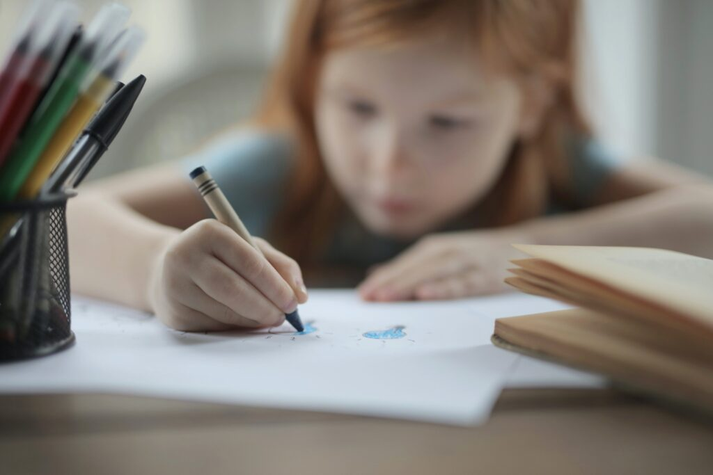 A young child using a crayon.