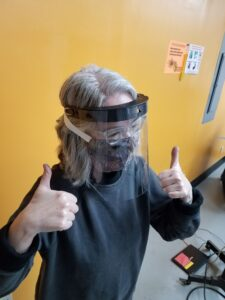 Pamela Cohen tests a face shield for fit at Maker Works. Image credit: Maker Works.