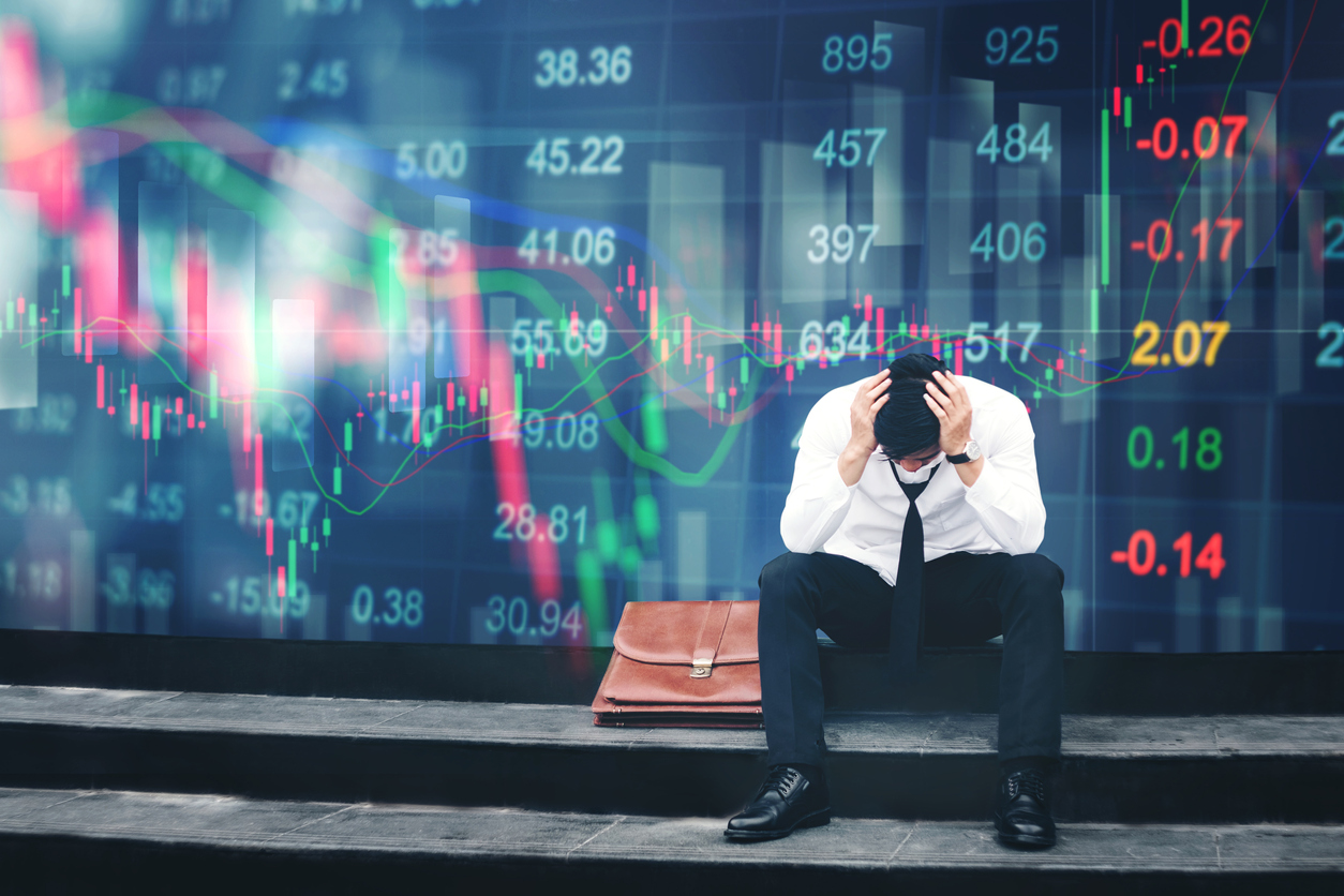 Stressed businessman sitting in front of digital stock market downturn. Image credit: iStock