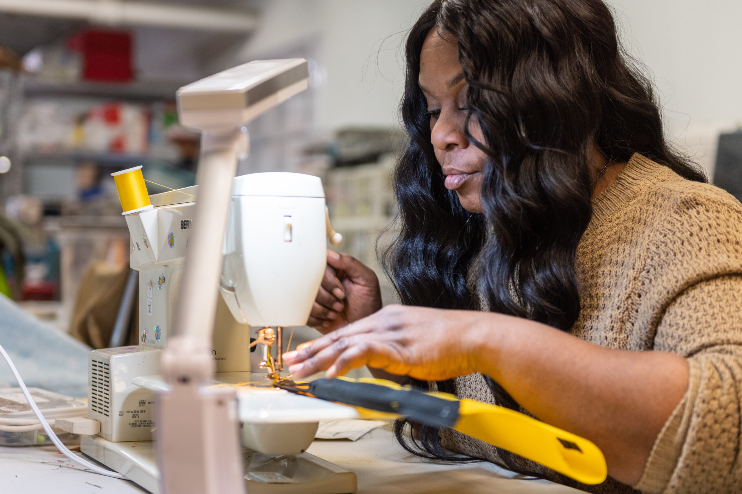 """Program participant Yolanda practices her sewing skills at Sew Great Detroit at Alternatives For Girls. """"It's motivation, and it's a new skill for me. Now, I'm teaching my daughters."""" Image credit: Eric Bronson, University of Michigan Photography"""