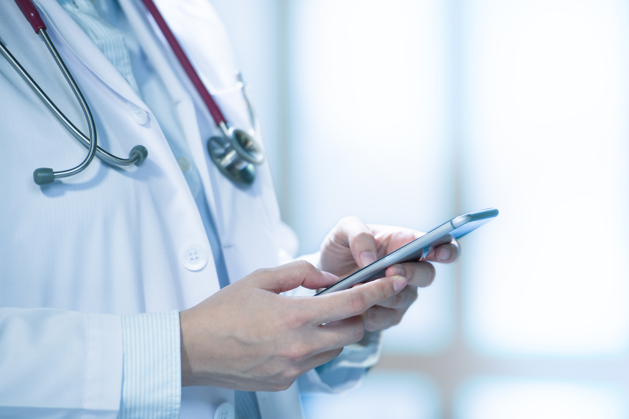 Medical doctor using smart phone for work in hospital. Image credit: iStock