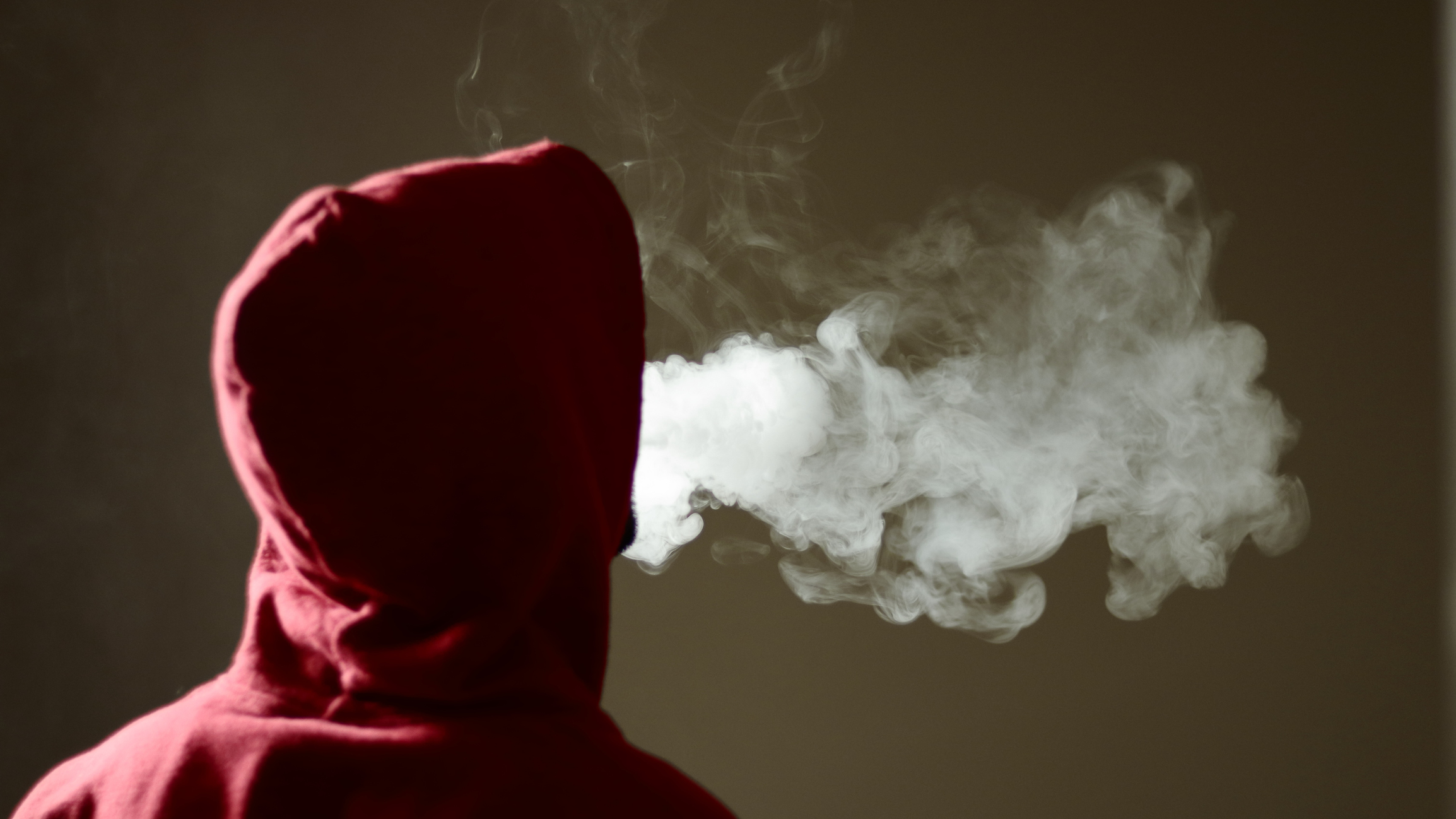 Young male in red hoodie vaping smoking, exhales thick vapor, isolated rear view. Image credit: property of Naveen Asaithambi