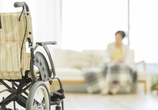 Woman and a wheelchair in an empty nursing home. Image credit: iStock