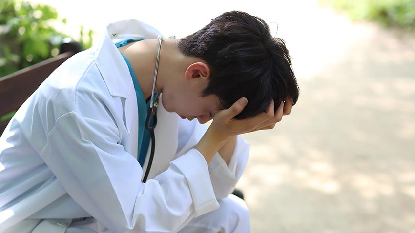 Young doctor stressed on park bench. Image credit: Getty Images