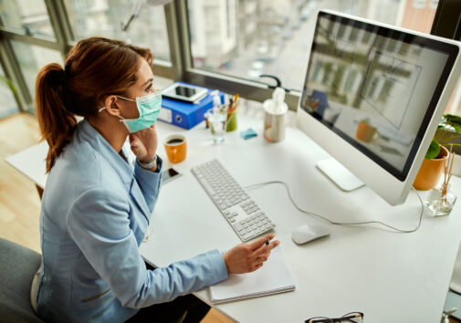 Architect planning while wearing face mask. Image credit: iStock