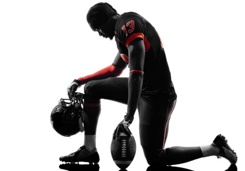 American football player kneeling in silhouette shadow on white background. Image credit: iStock