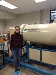 Student Bowen next to accelerator mass spectrometer.