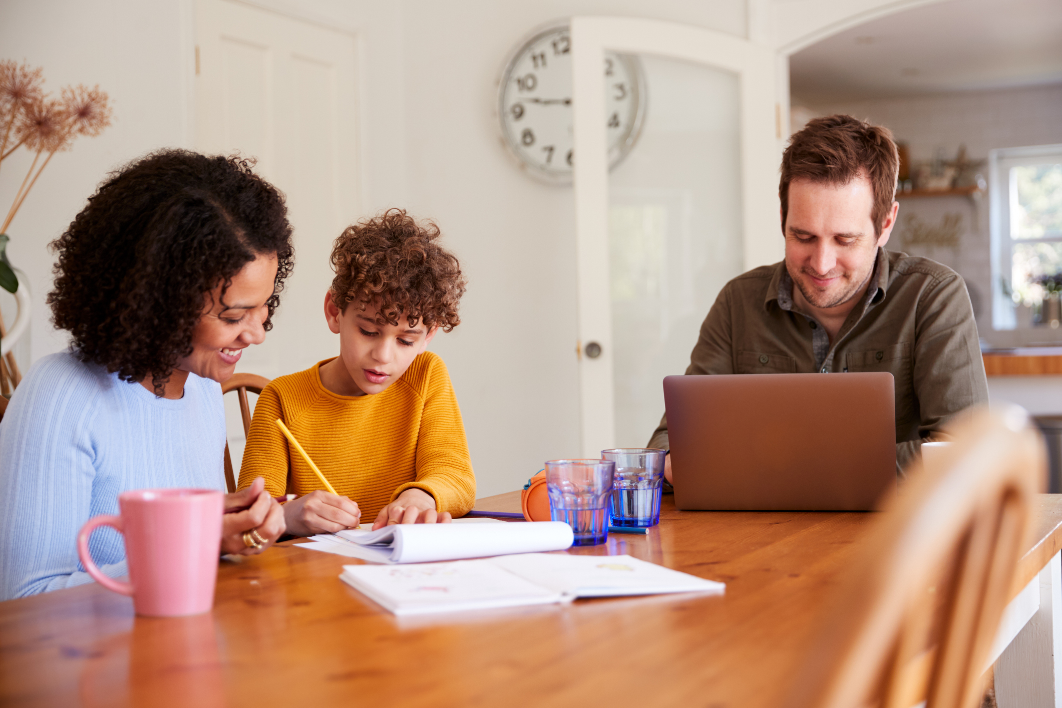 Parents helping child with schoolwork. Image credit: iStock