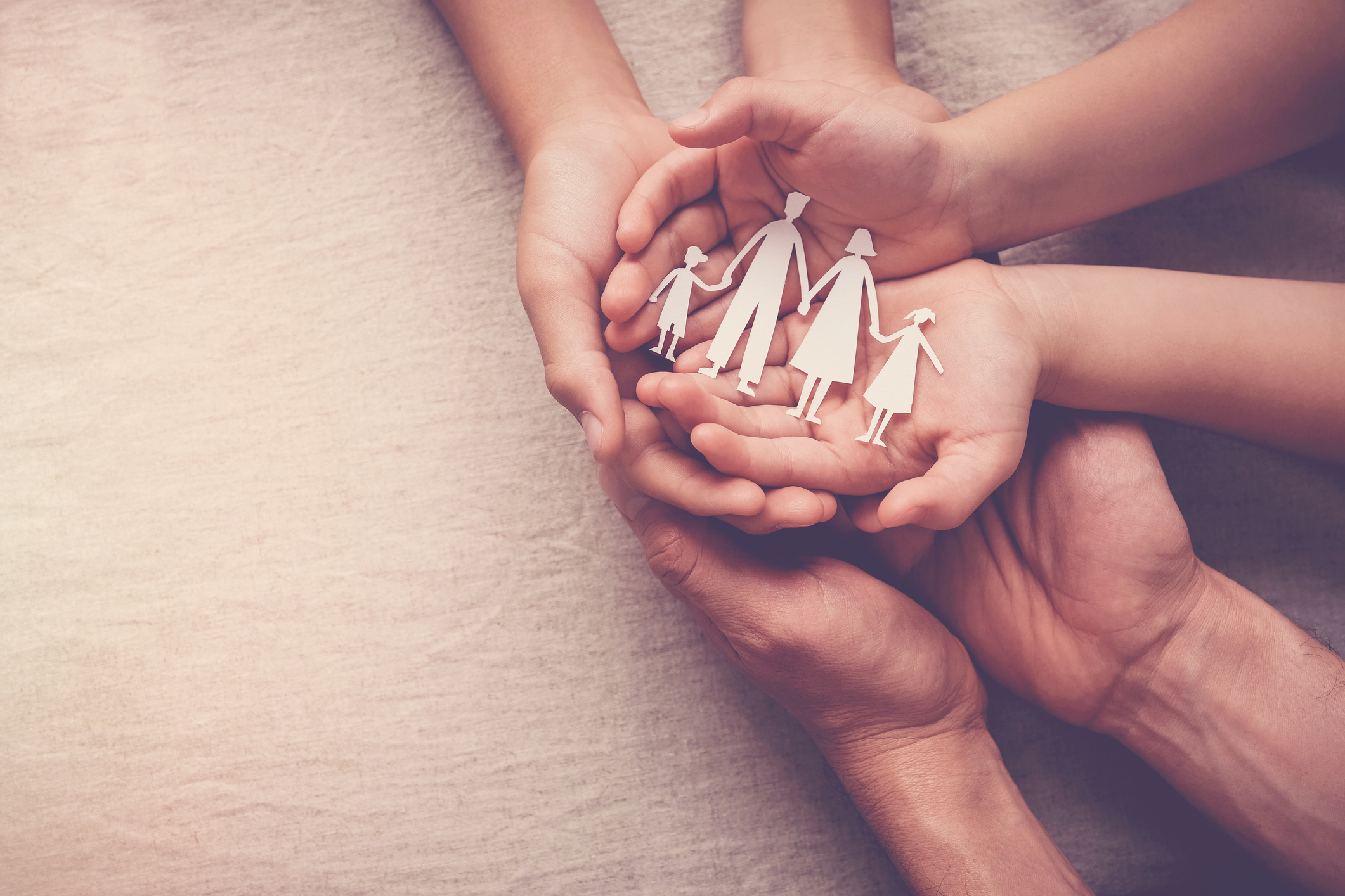 Foster care concept image, hands holding cutout of a family unit. Image credit: iStock
