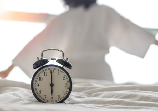 Circadian rhythm concept image, woman waking up next to clock. Image credit: iStock