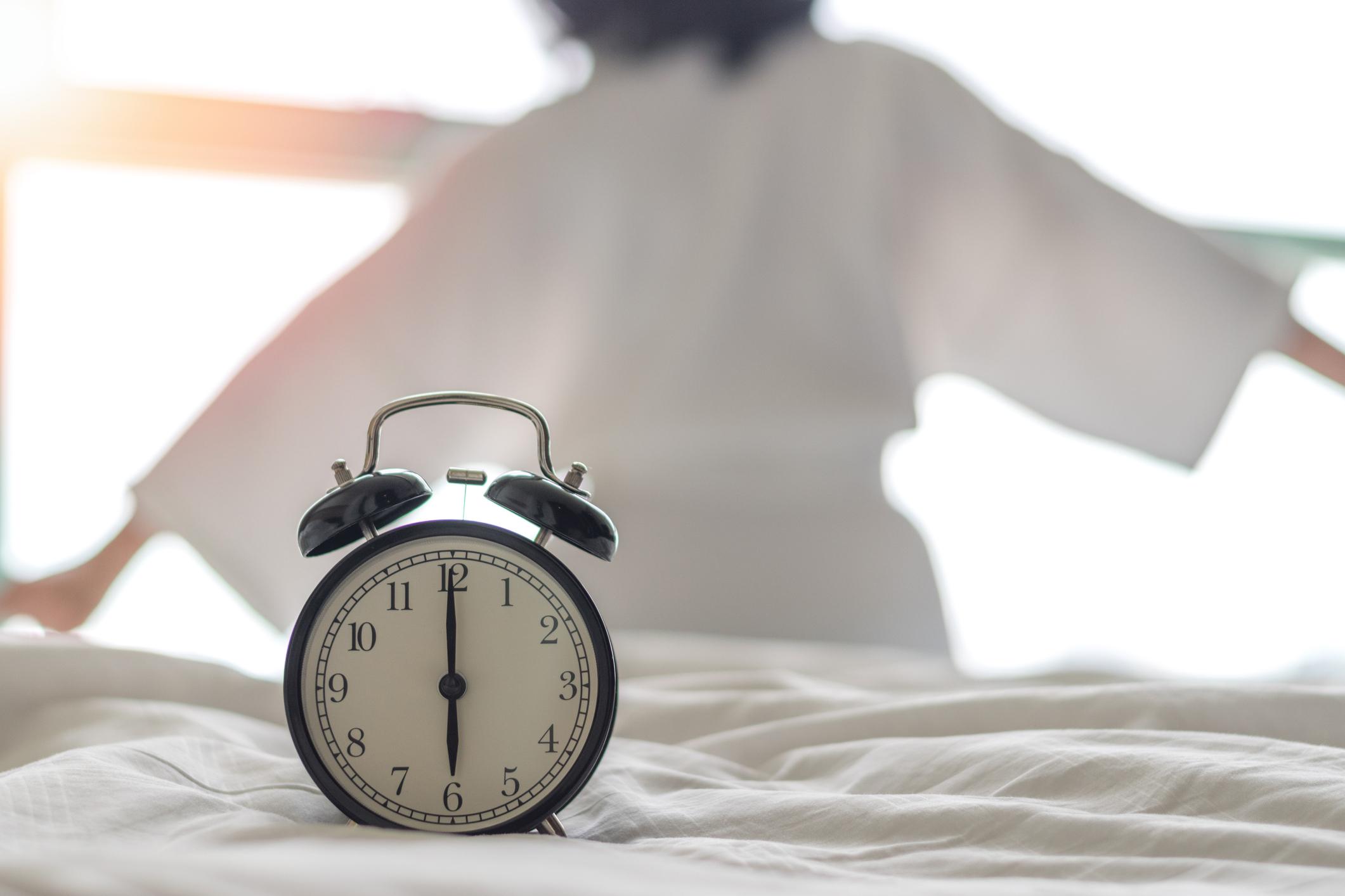 Circadian rhythm concept image, woman waking up next to clock. Image credit: iStock