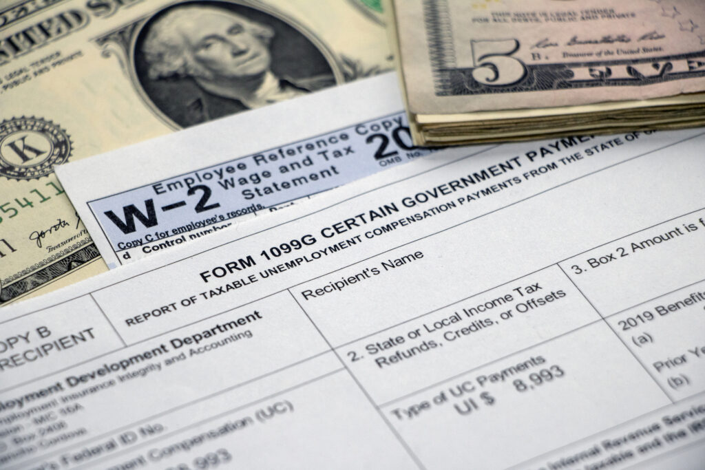 iStock Image: Closeup of a Form 1099G Certain Government Payments for unemployment benefits atop a W2 form and dollar bill, with stack of $5 bills.