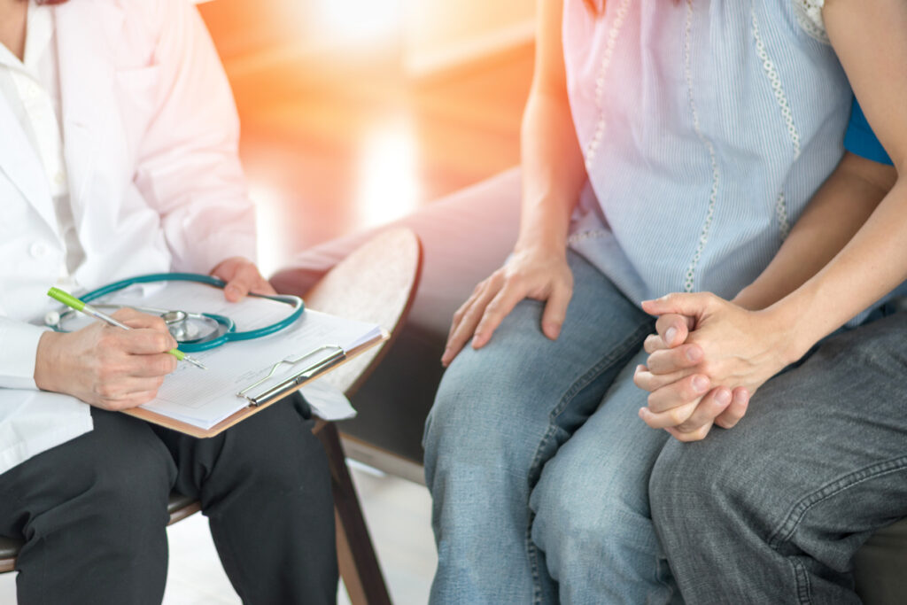 A couple holds hands while consulting with a doctor. Image credit: iStock