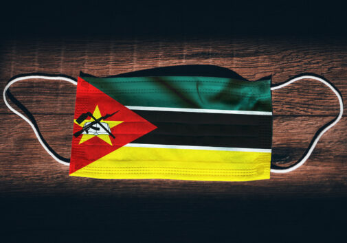 "Mozambique National Flag at medical, surgical, protection mask on black wooden background. Coronavirus Covid""u201319, Prevent infection, illness or flu. State of Emergency, Lockdown. Image credit: kovop58"