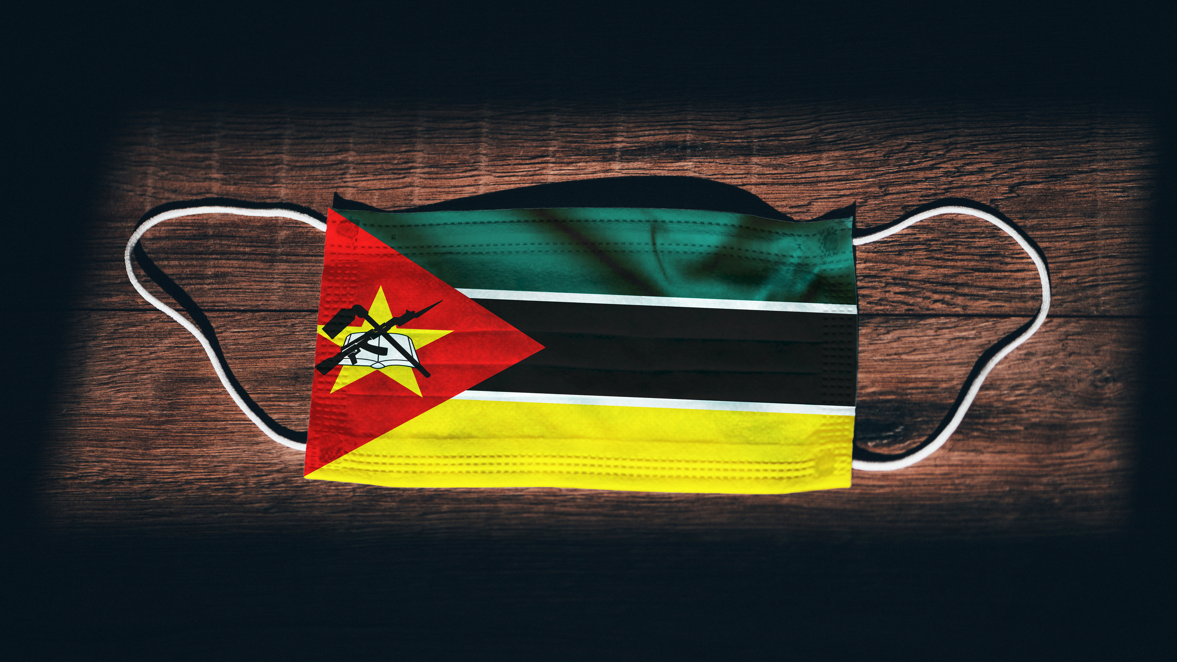 """Mozambique National Flag at medical, surgical, protection mask on black wooden background. Coronavirus Covid""""u201319, Prevent infection, illness or flu. State of Emergency, Lockdown. Image credit: iStock"""