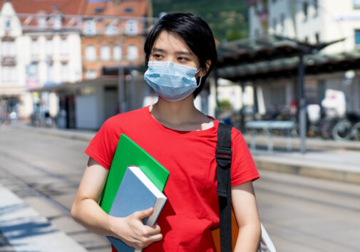 East asian male student wearing face mask. Image credit: iStock