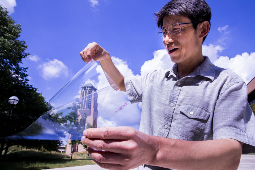 Jay Guo holds a sheet of flexible transparent conductor on the University of Michigan's College of Engineering North Campus.
