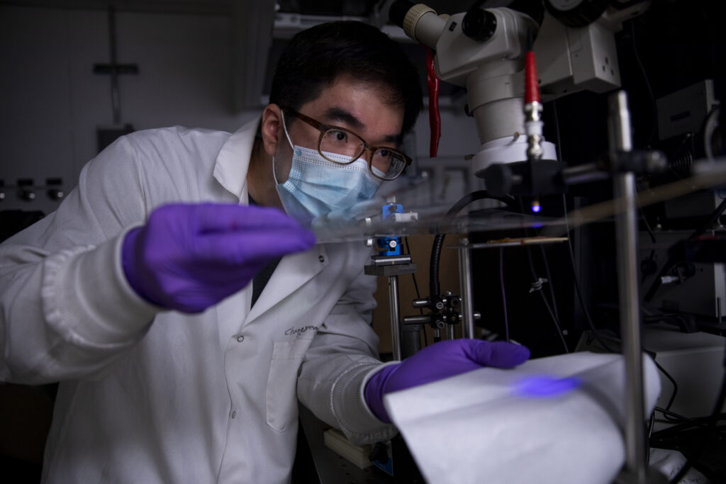 Changyeong Jeong, a graduate student in electrical engineering and computer science, measures how well light passes through a sheet of flexible transparent conductor.