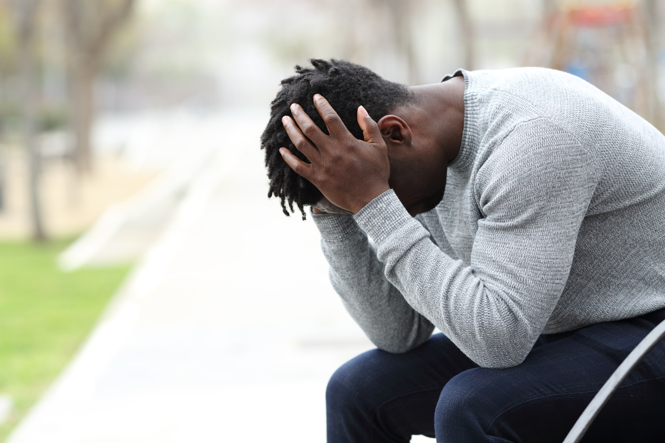 Sad man holding his head. Image credit: iStock