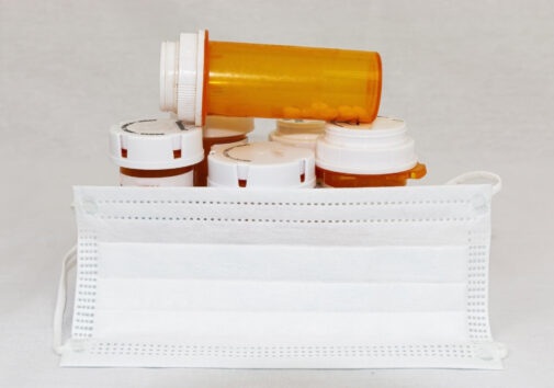 Pill bottles and a face mask. Image credit: iStock