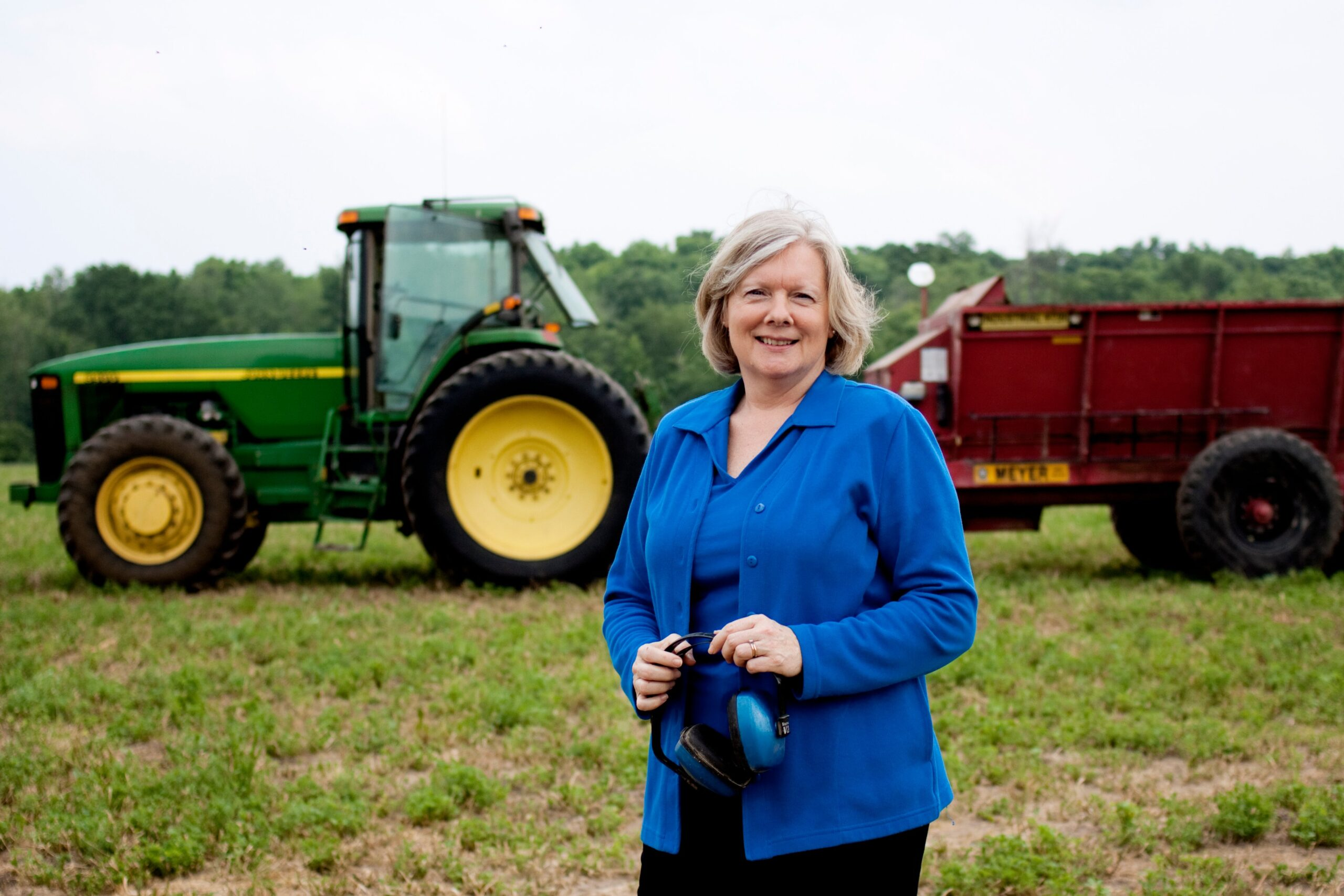 Marjorie McCullagh sanding in front of tractors on farmland. Image credit: U-M School of Nursing