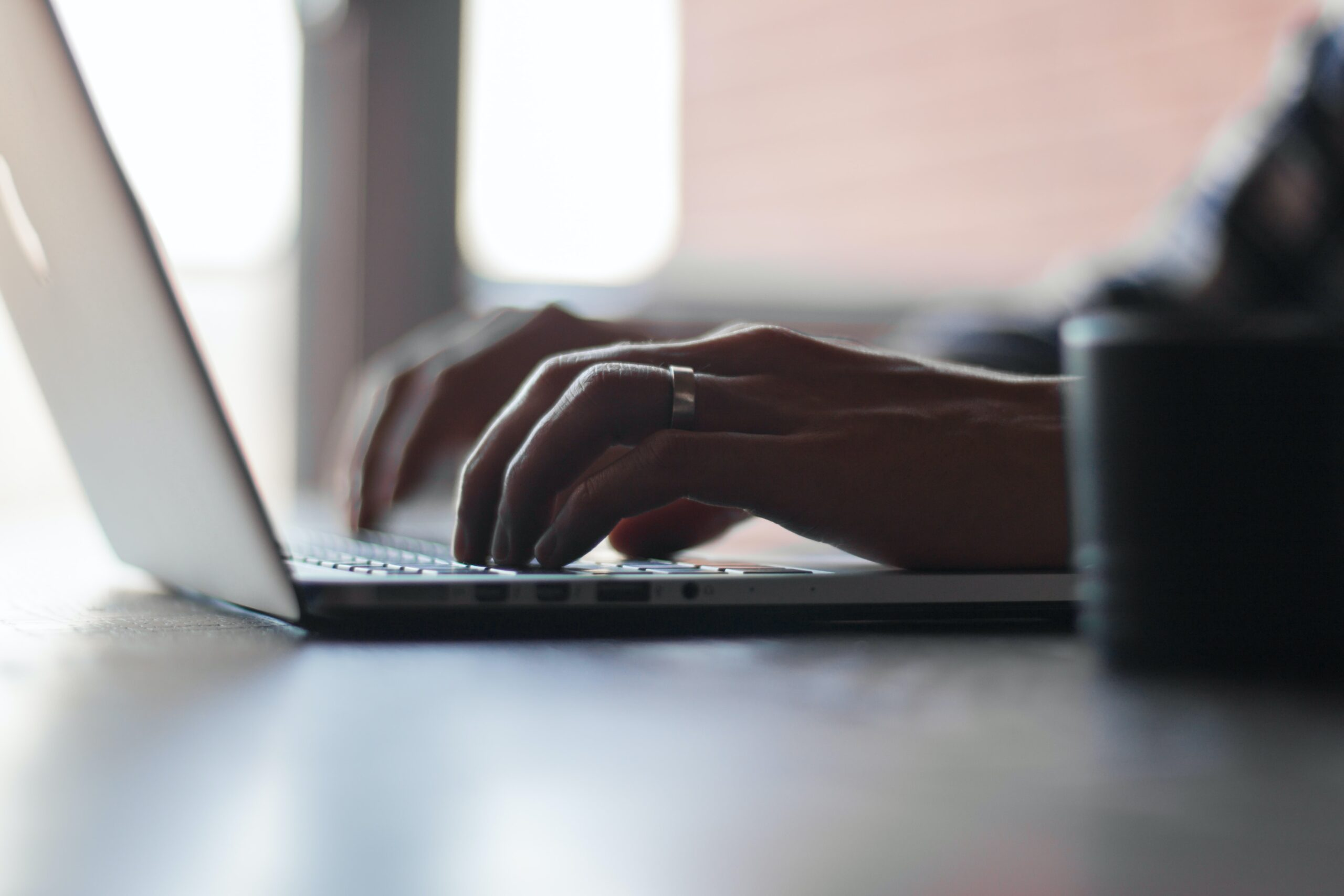 Hands of a person using a laptop. Image credit: UnSplash