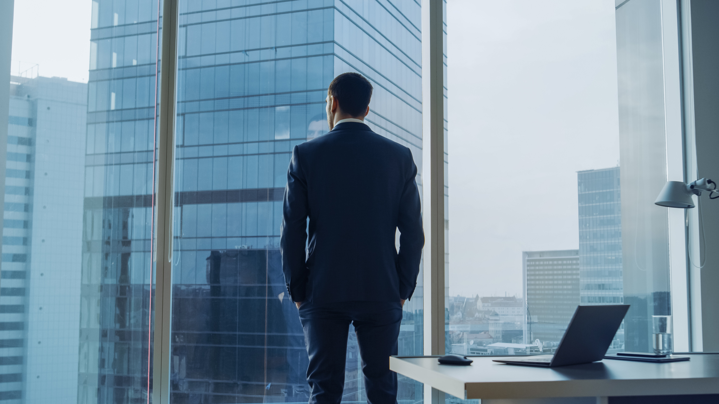 Back View of the Thoughtful Businessman wearing a Suit Standing in His Office, Hands in Pockets and Contemplating Next Big Business Deal, Looking out of the Window. Big City Business District Panoramic Window View. Image credit: iStock