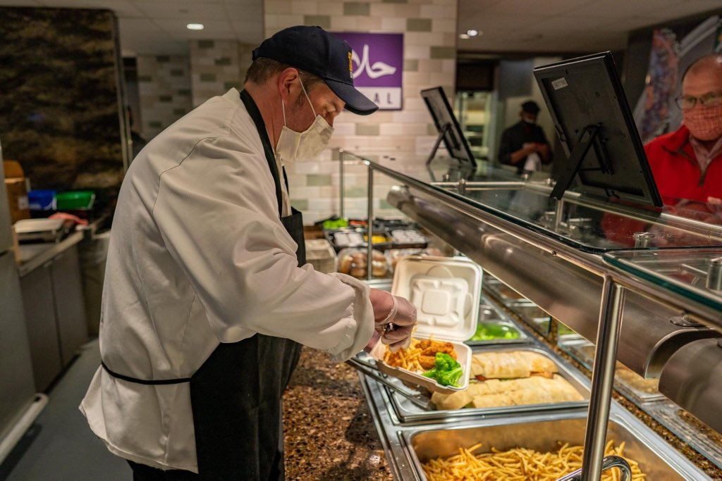 Dining hall server putting food into container. Image credit: MDining