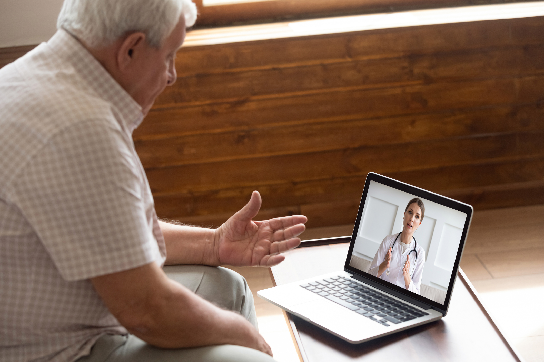 Focused older 80s patient consulting with doctor via video call. Image credit: iStock