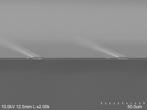 The electron microscope image shows the air (darkest gray) sandwiched between the gold backing at the bottom and the semiconductor at the top, supported on gold beams. Image credit: Dejiu Fan, Optoelectronic Components and Materials Group, University of Michigan