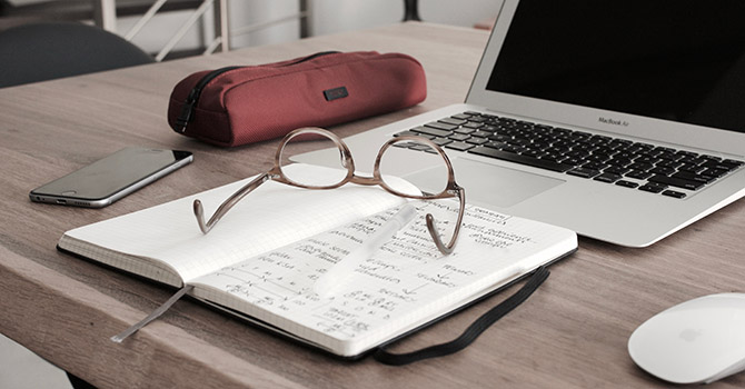 A book, glasses, phone, pencil case, and laptop on a desk. Image courtesy: U-M SPH