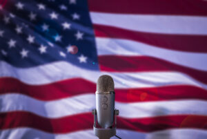 A microphone in front of a U.S. flag. Image credit: iStock